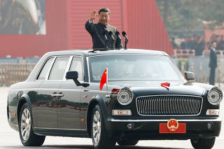 Chinese President Xi Jinping waves from a vehicle as he reviews the troops at a military parade marking the 70th founding anniversary of People's Republic of China