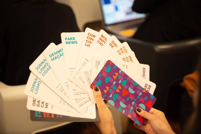 Mão segura uma série de cartões em leque