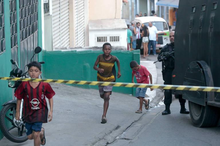 Crianças passam por Caveirão e policial durante a reconstituição da morte da menina Ágatha Félix, 8