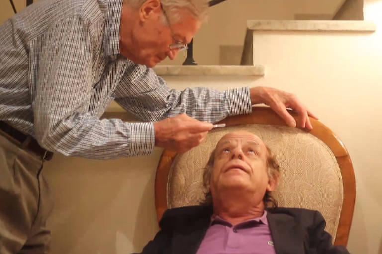 homem pinga colírio no olho de outro homem