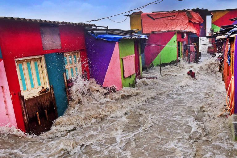 Maré alta entra em casa | Fotógrafo de Meio Ambiente do Ano | Onda invade vizinhança em Bandra, subúrbio de Mumbai, na Índia, carregando um pescador para fora de sua casa; a cidade está em risco de alagamentos em decorrência da mudança climática, com temperaturas aumentando e nível do mar subindo