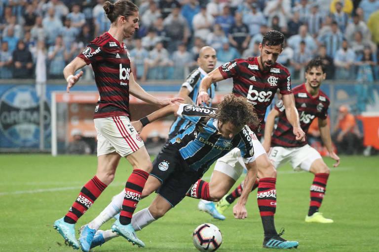 Disputa de bola entre o gremista Rafael Galhardo e o flamenguista Filipe Luís