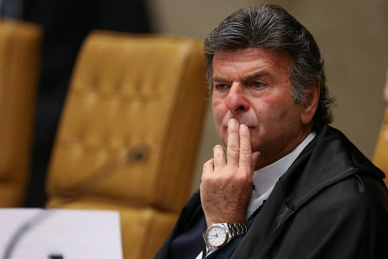 Luiz Fux, sentado, de toga, em frente a microfone e com dois dedos na altura da boca, com cara de pensativo