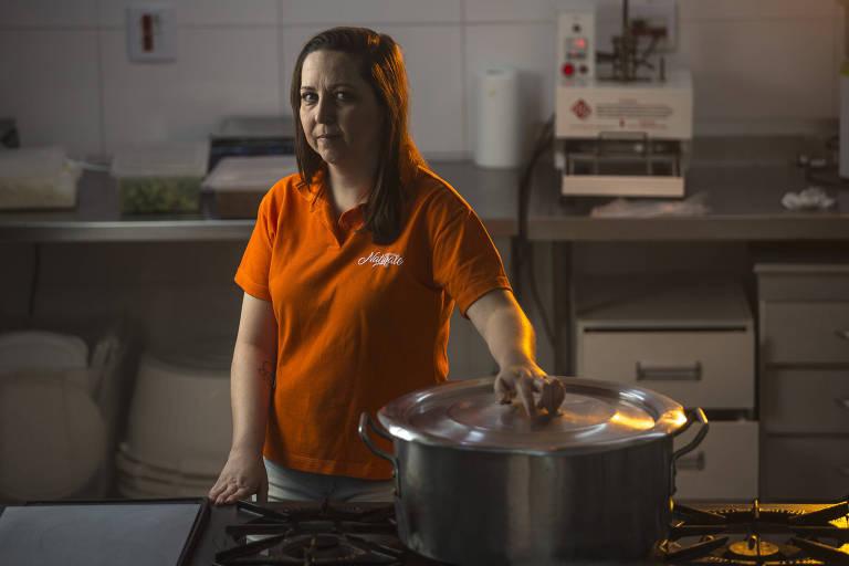 Mulher com camiseta laranja em cozinha