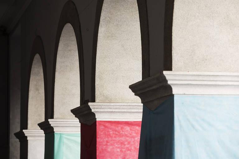 Detalhe de arcos de prédio antigo, com bases pintadas nas cores verde, vermelho e azul