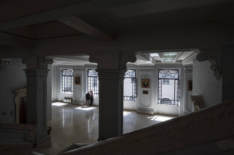 Vista interna de prédio antigo, com colunas e arcos em primeiro plano e quatro janelas altas em segundo plano; duas pessoas olham por uma das janelas para fora do prédio