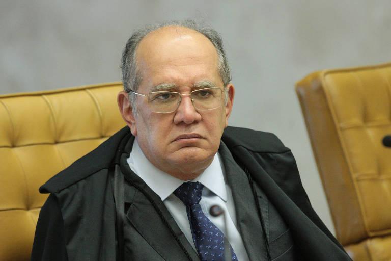 Ministro Gilmar Mendes usa óculos e está sentado em uma cadeira amarela