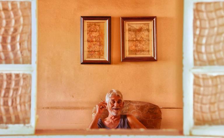 Fábio Negrão sentado em uma poltrona, com um cigarro na mão, na casa que era da sua mãe