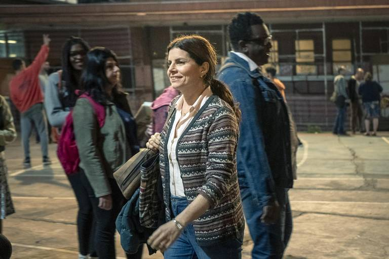 Lucia ( Debora Bloch ) cruza o pátio com vários alunos ao redor