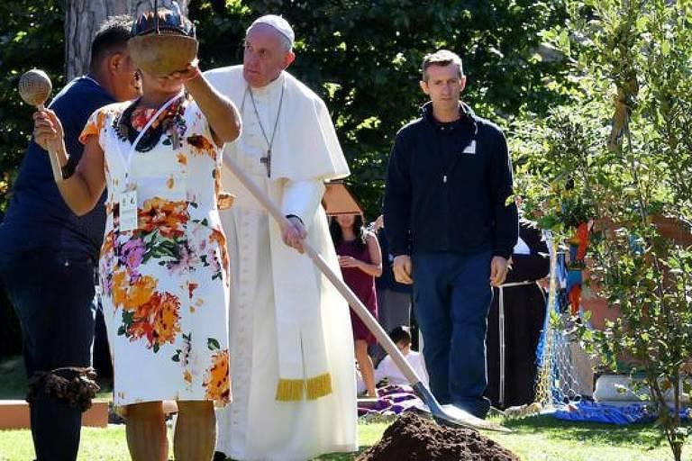Papa Francisco segura uma pá, em um jardim, e cava na grama para plantar uma árvore.