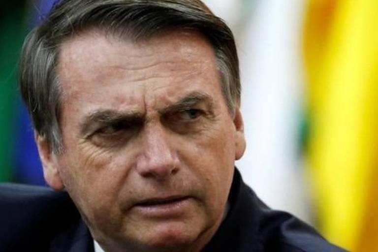 Bolsonaro franze a testa e olha para os lados.