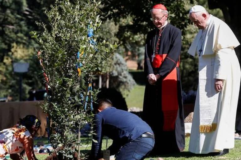 Enquanto duas mulheres estão agachadas na grama, plantando uma muda, o Papa observa.