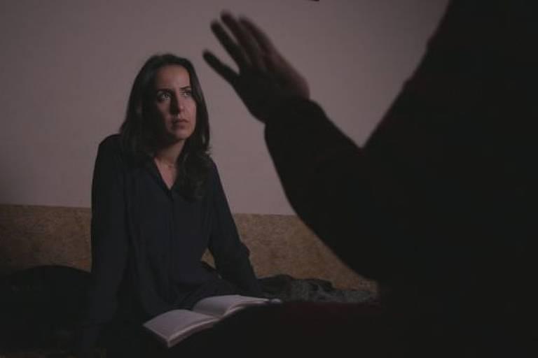 Foto mostra mulher sentada com caderno de anotações. Ela olha com atenção para a sombra de uma pessoa que está de costas para a imagem, aparentando falar