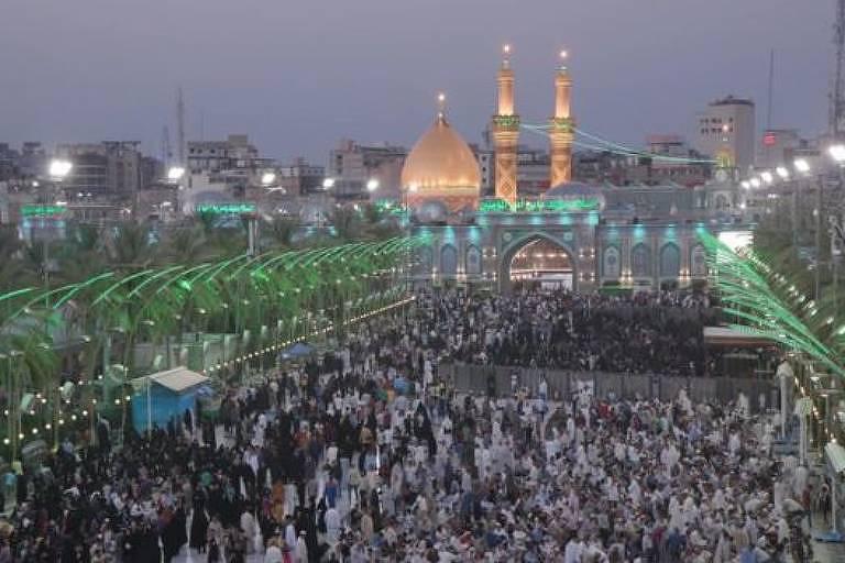 Em primeiro plano, peregrinos se reúnem em grande número. Ao fundo está o prédio da mesquita