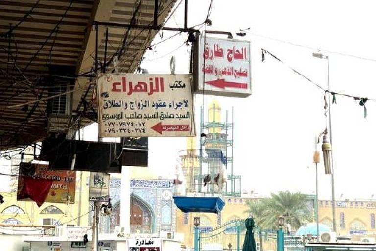 Placas com texto em árabe penduradas numa marquise de prédio na rua de Kadhimya. Ao fundo, céu ensolarado.