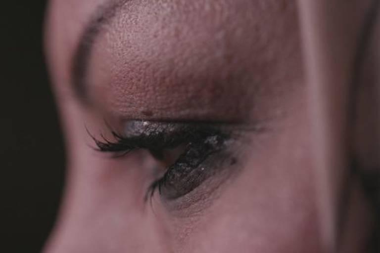 Perfil de mulher fotografado de perto, de modo que só é possível ver o olho esquerdo com maquiagem. O olho está para baixo.