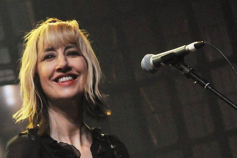 Com cabelos louros e franja, Kim Shattuck sorri diante de um microfone.