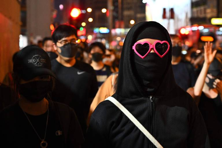 Ativista em Hong Kong cobre o rosto em manifestação depois do anúncio de lei que proíbe máscara em protestos