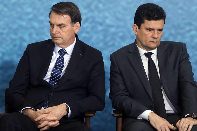 Sentados em cadeiras pretas, os dois de pernas abertas, Moro e Bolsonaro olham para direções opostas.
