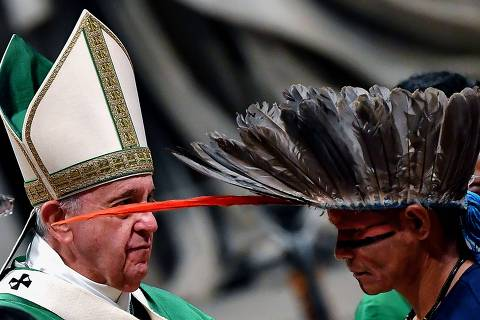 A representative of one of the Amazon Rainforest's ethnic groups (R) wals past Pope Francis as he takes part in a mass on October 6, 2019 at St. Peter's Basilica in the Vatican, for the opening of the Special Assembly of the Synod of Bishops for the Pan-Amazon Region. - Pope Francis will gather Catholic bishops at the Vatican on October 6 to champion the isolated and poverty-struck indigenous communities of the Amazon, whose way of life is under threat. (Photo by Tiziana FABI / AFP)