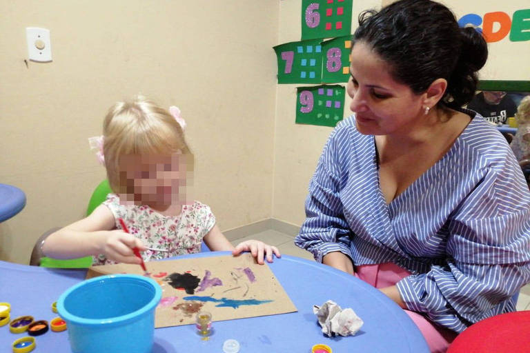 Menina brinca com mulher em uma mesa usando material de pintura
