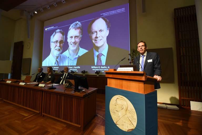 Thomas Perlmann, secretário do Comitê do Nobel, anuncia os ganhadores do Nobel de Medicina: William Kaelin, Gregg Semenza e Peter Ratcliffe