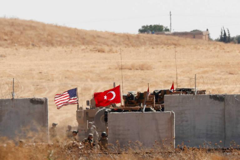 Bandeiras dos Estados Unidos e da Turquia são exibidas durante uma patrulha conjunta dos dois países no norte da Síria