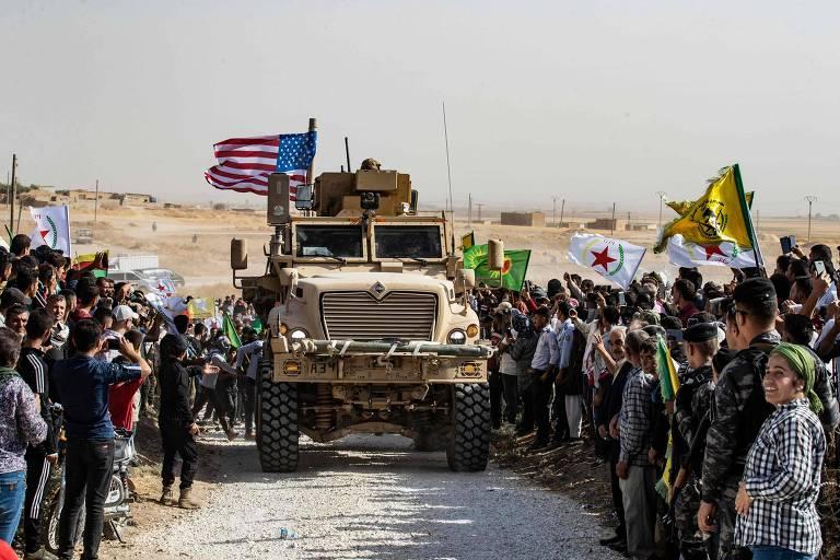 Curdos sírios próximos a veículo militar norte-americano em protesto contra a ameaça de invasão turca em província curda na Turquia