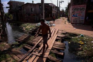 Morador cruza passagem sobre esgoto a céu aberto em bairro de Belém