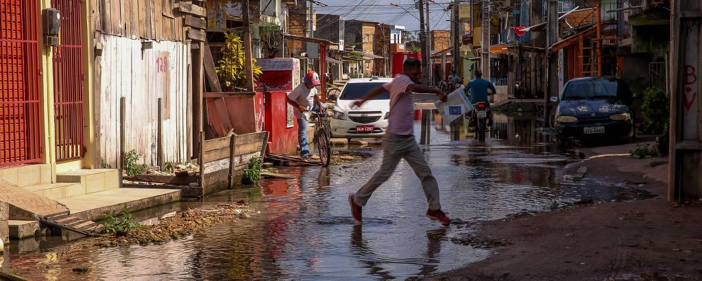 Pessoa atravessa rua repleta de água e lama, ladeada por casas de alvenaria e madeira