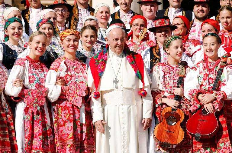 Papa Francisco sorri ao posar com adereço no pescoço ao lado de mulheres com vestes típicas, que também sorriem