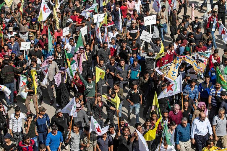 Curdos fazem manifestação na cidade síria de Ras al-Ain contra a Turquia pouco antes do início dos ataques