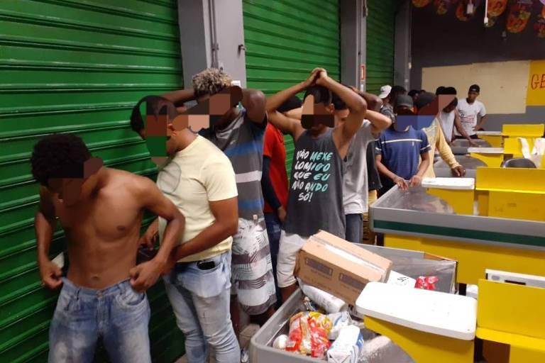Homens enfileirados, estão sendo  vistoriados pela PM em um supermercado