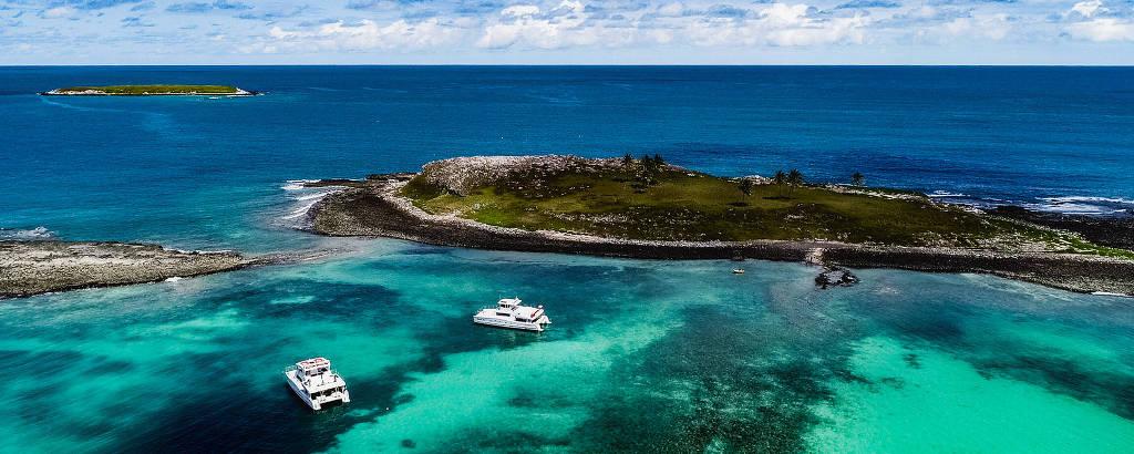 Área com mar cristalino, barcos e ilha