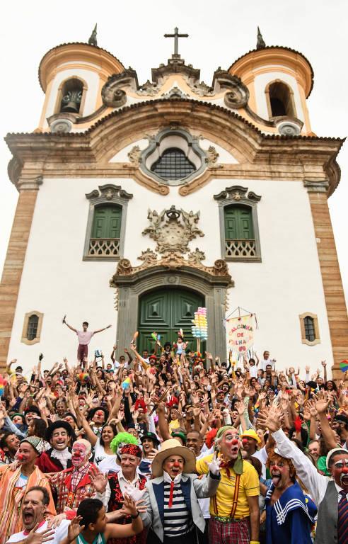 Multidão de palhaços reunida em frente a igreja barroca