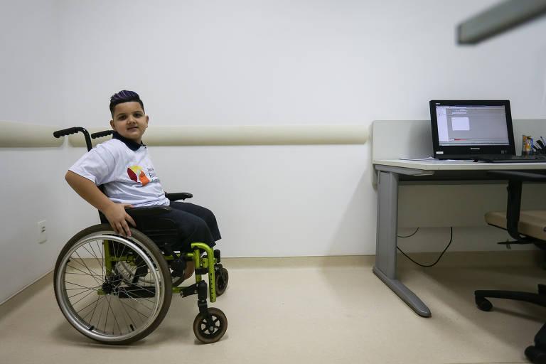Enzo está em uma cadeira de rodas infantil, com detalhes verdes, aguardando em uma sala de consulta o momento de testar suas próteses