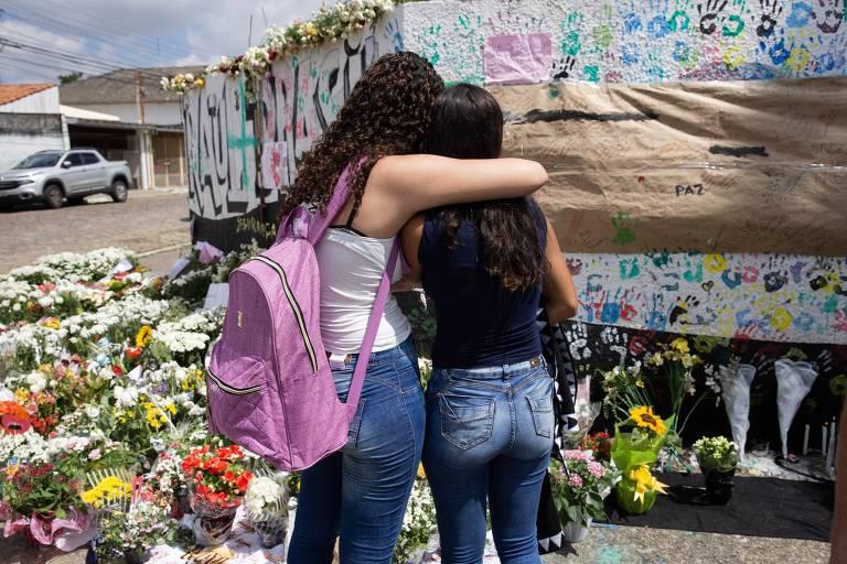 Alunas em frente a homenagens a vítimas do ataque na escola Raul Brasil, em Suzano
