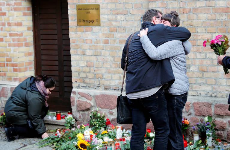 Uma mulher está agachada, colocando mais uma flor no chão. Ao lado dela, em pé, uma mulher chora abraçada a um homem