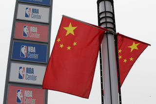 NBA logos are seen next to Chinese national flags outside a NBA-themed lifestyle complex on the outskirts of Tianjin