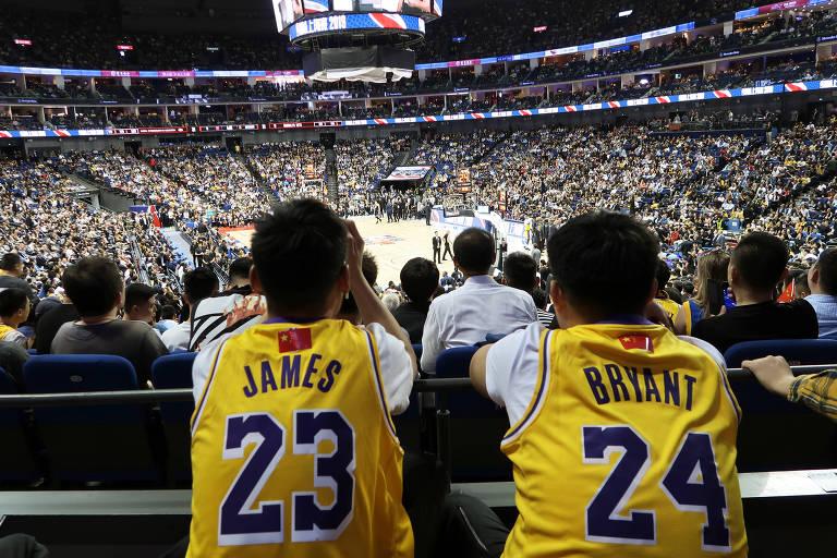 Fãs de LeBron James e Kobe Bryant vestem camisas personalizadas durante jogo entre Los Angeles Lakers e Brooklyn Nets em Xangai