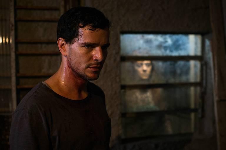 Um homem está no meio de uma sala escura e, atrás de uma janela de vidro, uma morta o observa