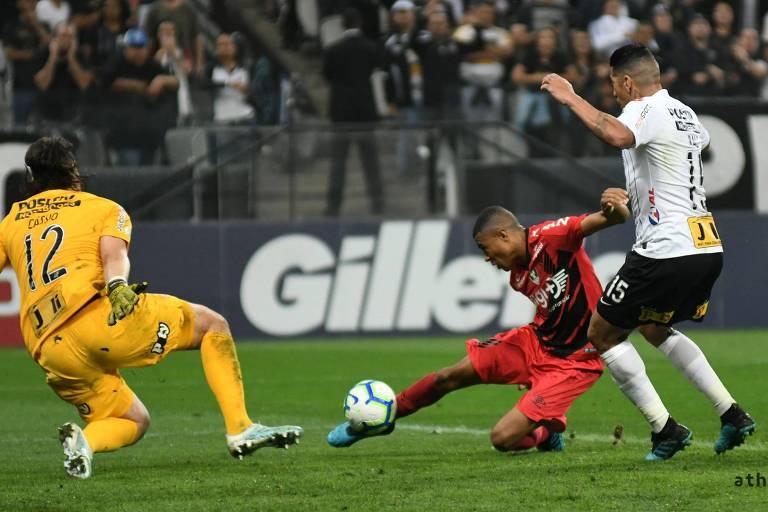 Marcado por Ralf, Erick chuta para superar Cássio e marcar o segundo gol do Athletico-PR sobre o Corinthians, no estádio em Itaquera
