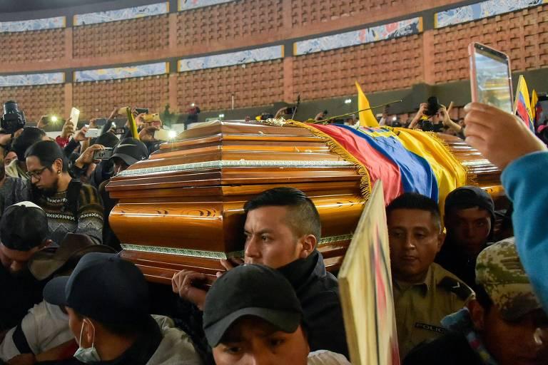 Policiais que foram detidos por manifestantes carregam caixão