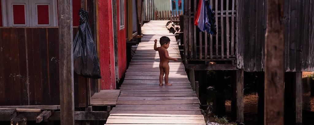 Criança pequena nua vista ao longe caminha por tábuas entre barracos construídos em palafitas, com lixo e água suja passando embaixo, num dia de sol