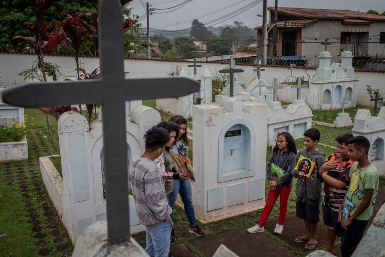 Jovens frequentadores leem entre as lápides do Cemitério Colônia