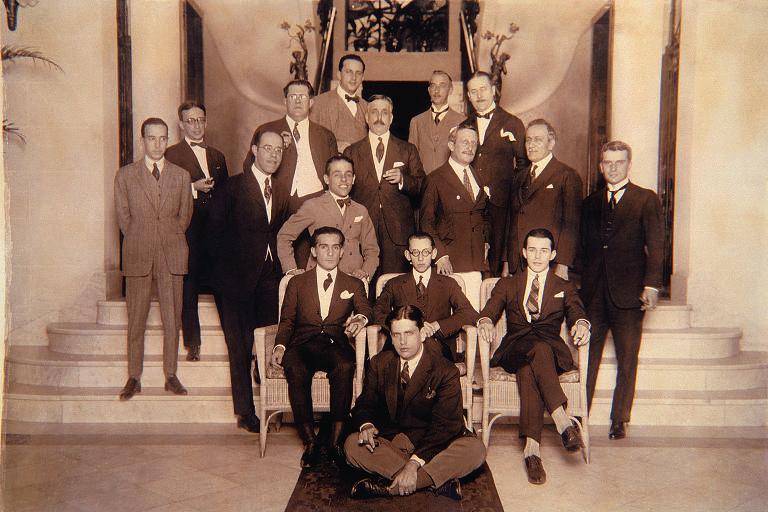 Homens de terno posam para foto enfileirados em escada