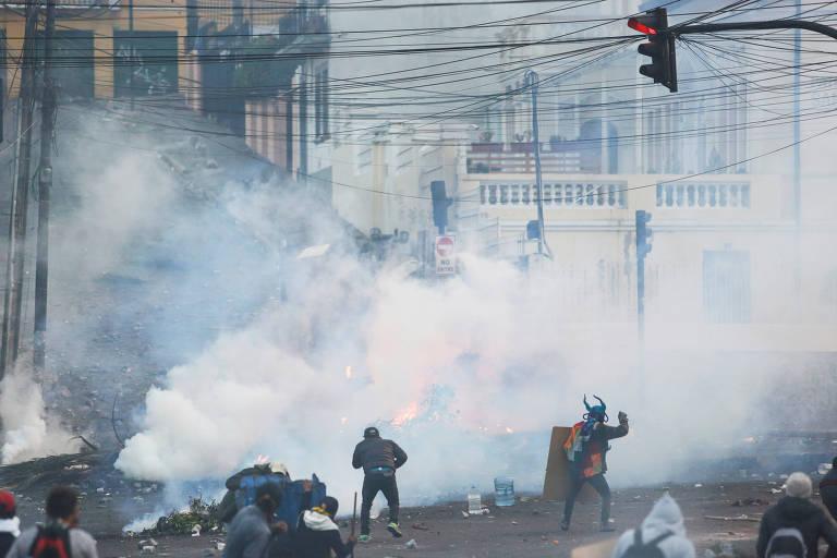 Policiais e manifestantes aparecem em meio a nuvem de fumaça numa rua de Quito