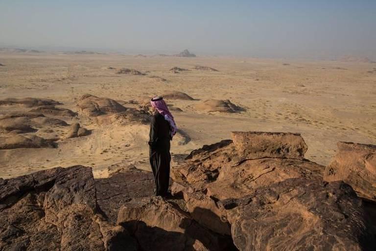 Homem em cima de uma pedra, no deserto.