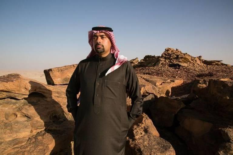 Arqueólogo árabe posa para foto em meio às rochas.