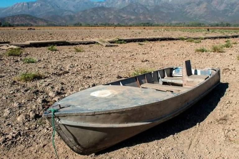 Barco de madeira abandonado em meio a lugar desértico